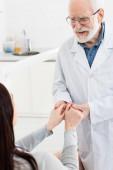 veselý starší zubař držící pacienta za ruce na zubní klinice
