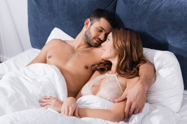 Muscular man hugging smiling girlfriend in bra on bed stock vector