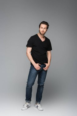 Full length of bearded man in jeans and black t-shirt posing while looking away on grey stock vector