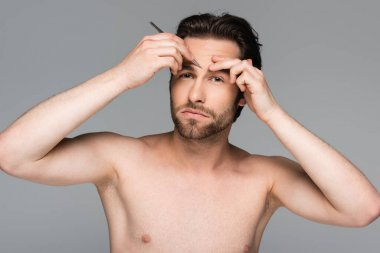 Bearded and shirtless man tweezing eyebrow isolated on gray stock vector