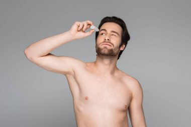 Shirtless man with closed eye applying eye drops isolated on grey stock vector