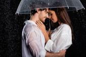 romantikus fiatal felnőtt pár álló eső esernyő és ölelés fekete háttér