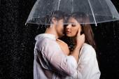 romantický mladý dospělý pár stojící v dešti s deštníkem a smyslně líbání na černém pozadí