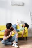 muž drží dálkový ovladač a při pohledu na klimatizaci v blízkosti africké americké přítelkyně mává novinami, zatímco trpí horkem