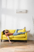 muž drží dálkové ovládání, zatímco leží na žlutém gauči a trpí horkem v obývacím pokoji