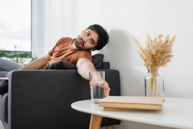 man reaching glass of water on blurred coffee table while suffering from heat