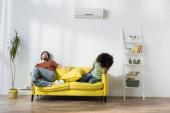 Erschöpftes gemischtrassiges Paar sitzt auf Sofa und leidet unter Hitze im Sommer