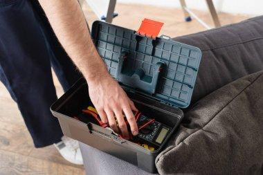 Becerikli adamın araç kutusundan dijital çokölçer alışının kırpılmış görünümü