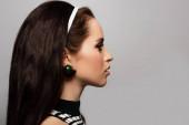 profil krásného mladého modelu pózujícího izolovaně na šedi
