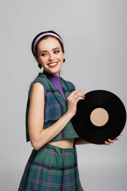 Happy young woman in headband holding retro vinyl disc isolated on grey stock vector
