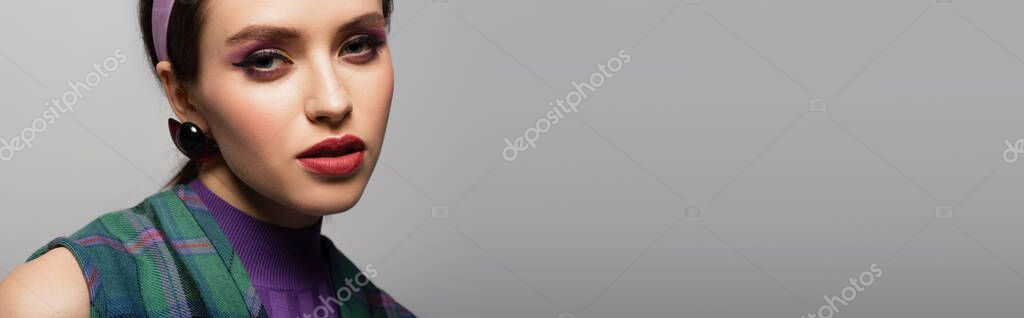 Young woman in purple headband and earring looking at camera isolated on grey, banner stock vector