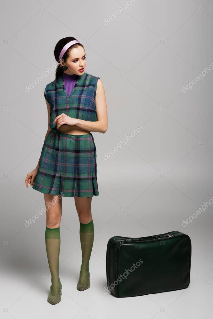Full length of brunette woman in retro outfit standing near green suitcase on grey stock vector