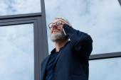 Reifer Geschäftsmann mit Brille und grauen Haaren spricht auf dem Smartphone in der Nähe moderner Gebäude
