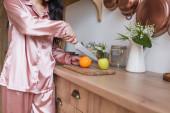 částečný pohled mladé ženy v růžovém hedvábí pyžama řezání ovoce v kuchyni