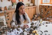 mladá asijská žena ve sluchátkách sedí na stole a pomocí notebooku v blízkosti notebooku v kuchyni