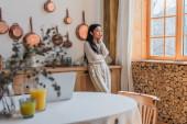 přemýšlivý mladý asijské žena v halence a kalhoty stojící se sluchátky a drží ruku v blízkosti obličeje v kuchyni