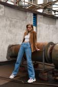 Blonde Frau in Jeans, Wildlederblazer und trendigen Turnschuhen posiert auf dem Dach