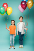 šťastné děti držící barevné balónky na modré