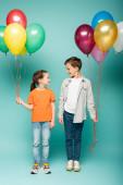 šťastné děti při pohledu na sebe, zatímco drží barevné balónky na modré