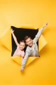 šťastné děti drží za ruce a usmívají se dírou na žlutém pozadí