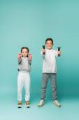 šťastné děti ve sportovním oblečení a tenisky cvičit s činkami na modré
