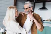 Lächelnde Frau schaut Ehemann beim Tanzen zu Hause an