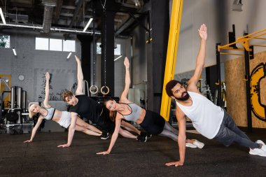 group of interracial people training in side plank pose in gym