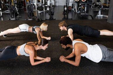 multiethnic people in sportswear training in plank pose in sports center
