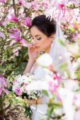 Mladá nevěsta v závoji stojící poblíž kvetoucího stromu magnólie