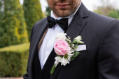 Ausgeschnittene Ansicht von boutonniere auf Jacke des Bräutigams im Freien