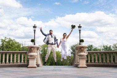 Parkta buket atlayan mutlu yeni evliler.