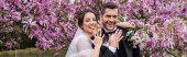 Veselá nevěsta a ženich ukazující prsteny a dívající se na kameru poblíž stromů magnólie, prapor