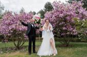 Šťastné novomanželé stojí blízko pádu kytice v parku
