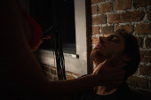 passionate woman with flogging whip touching face of young man near brick wall at night