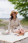vidám nő szalma kalap és fülhallgató segítségével laptop, miközben ül piknik takaró közelében okostelefon, napszemüveg és könyv