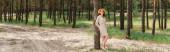 plná délka veselé mladé ženy v slamáku stojící v lese, prapor
