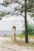 full length of smiling young woman adjusting straw hat and standing in woods near lake