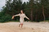 teljes hossza pozitív fiatal nő napszemüvegben kezében szalma kalap és séta erdő közelében