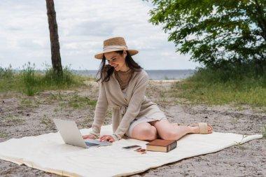 Akıllı telefon, güneş gözlüğü ve kitap yanında piknik battaniyesinde otururken bilgisayarını kullanan saman şapkalı ve kulaklı mutlu bir kadın.