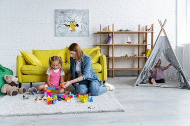 kindergarten teacher playing building blocks with preschooler girl while kid with down syndrome sitting in tipi