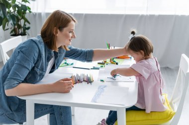 happy kindergarten teacher reaching disabled child with down syndrome molding plasticine on paper