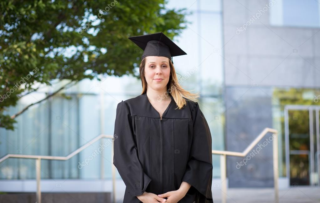 Portrait of female college student in graduation cap and gown on ...