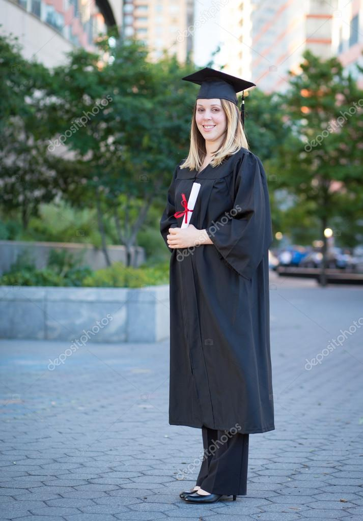 Portrait of female college student in graduation cap and gown ho ...