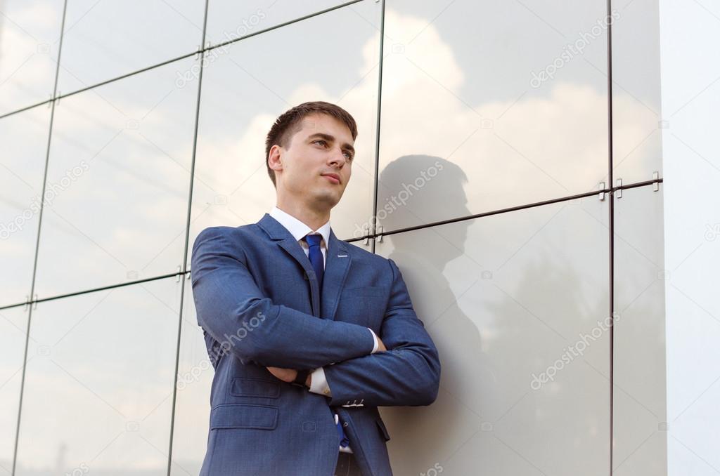 Abbigliamento Ufficio Uomo : Economista di successo giovane in piedi in uomo fiducioso interni