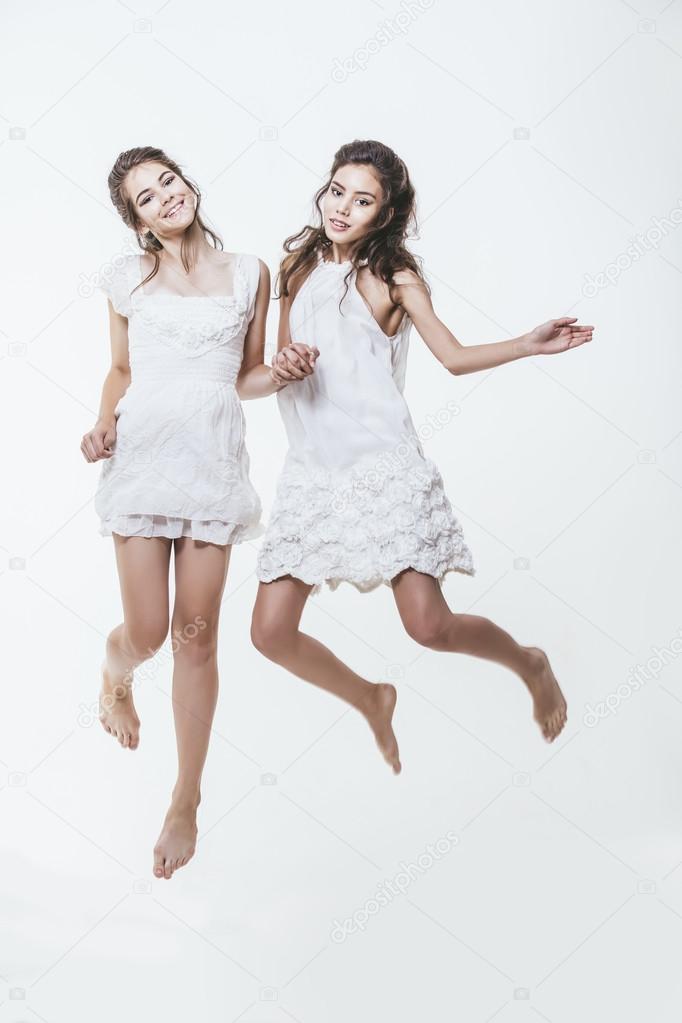 8609811460c Όμορφα νεαρά κορίτσια σε λευκό φορέματα μεταπηδήσετε ψηλά και προκλητικά — Φωτογραφία  Αρχείου