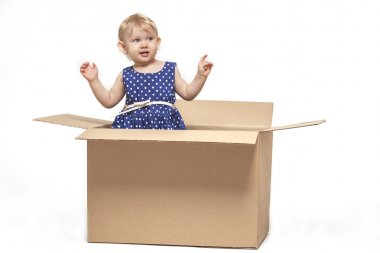 A small child in cardboard boxes