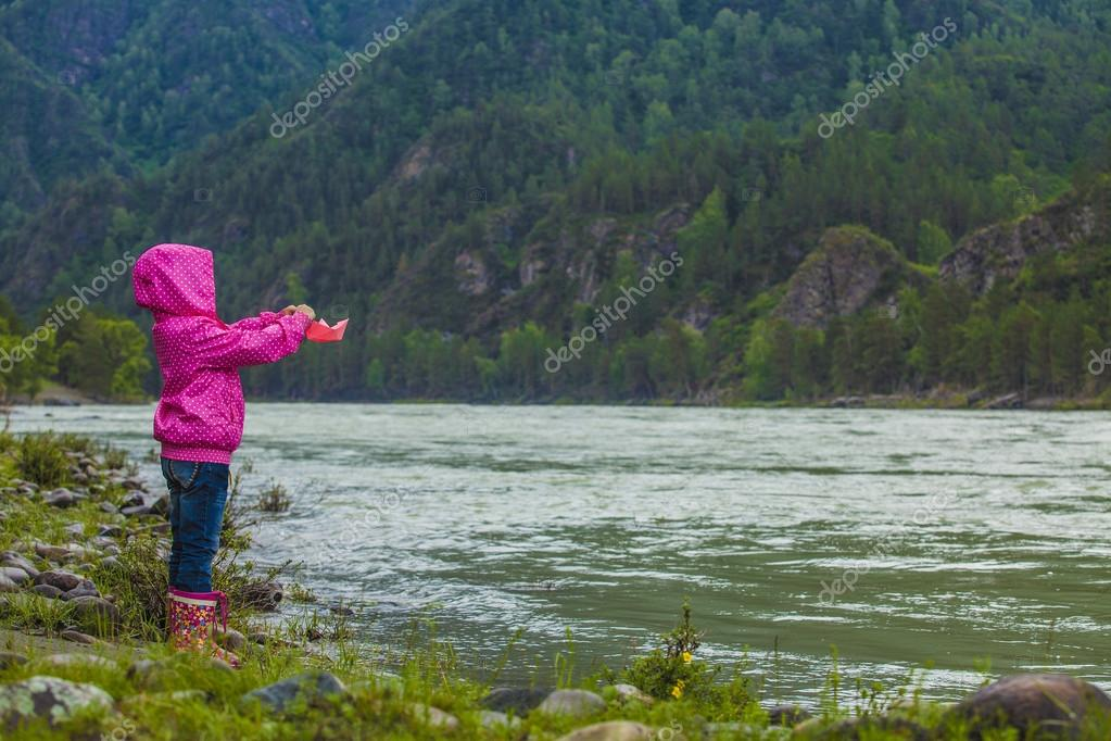 The baby launches a paper boat in a mountainous river