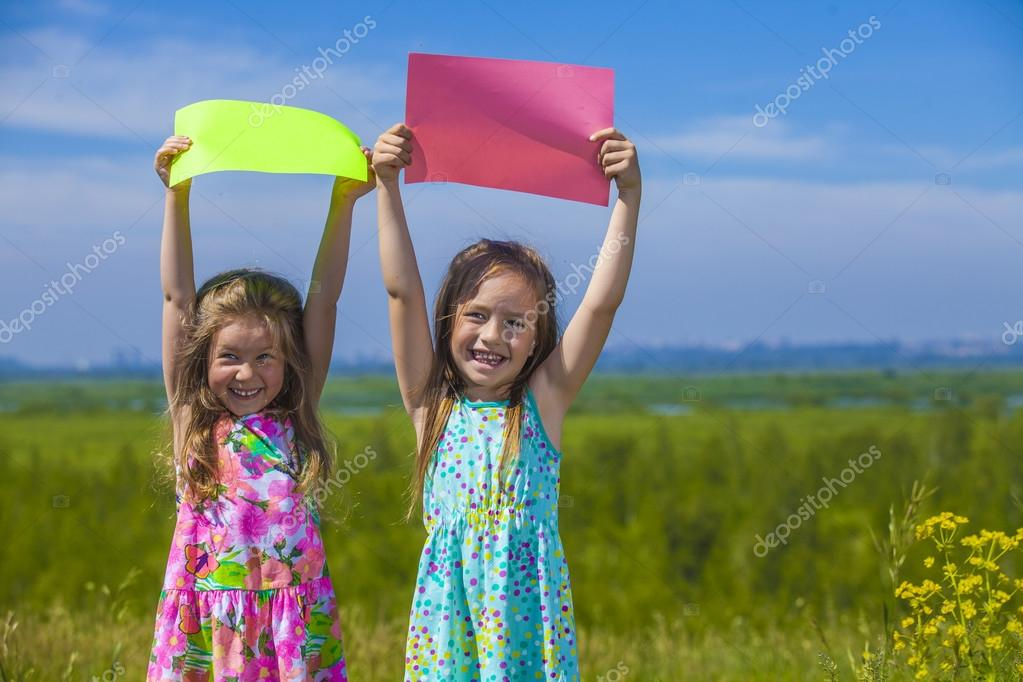 Two baby girls in summer dresses on the nature of holding the co