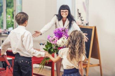 Boy and girl children give flowers as a school teacher in teache