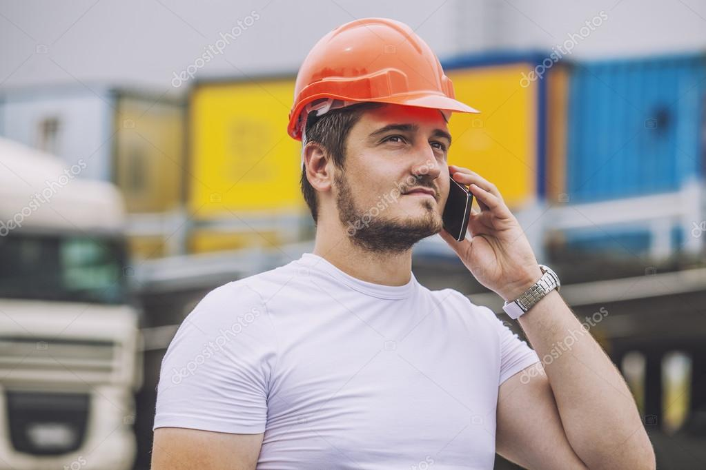 Builder man working with a cell phone in a protective helmet